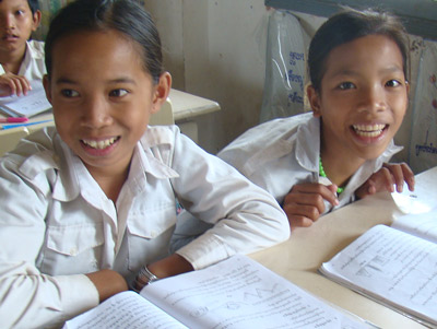 Girls smiling while at their desks in the classroom